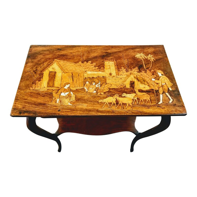 Antique rosewood parlor table with cabriole jambes (French legs that were introduced in French furniture in the late Louis XIV style) and a shaped lower shelf. The top features a sadeli (marquetry) village goat herding scene with a background showing mud architecture and a pair cooking at a pot over a fire. The scene is created with various woods and bone.  Sadeli, or marquetry, is a folk art specialty of craftspeople in Surat, Gujarat, India. Surat was the first headquarters and trading outpost established by the English East India Company in 1608, which led to British Raj in India.