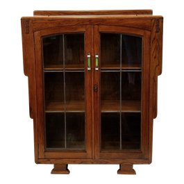 This oak display cabinet / bookcase was made in England in the late 1920s. The sharp geometrics, as this piece displays, gave way to softer, rounded forms through the 1930s. The pulls are brushed aluminum wrapped green Bakelite (slightly marbleized such as created by the Catalin company) with black enamel. The top front corners feature Art Deco floral appliques. The glazed doors feature rolled glass with lead. The lock is in working order and a key is included.