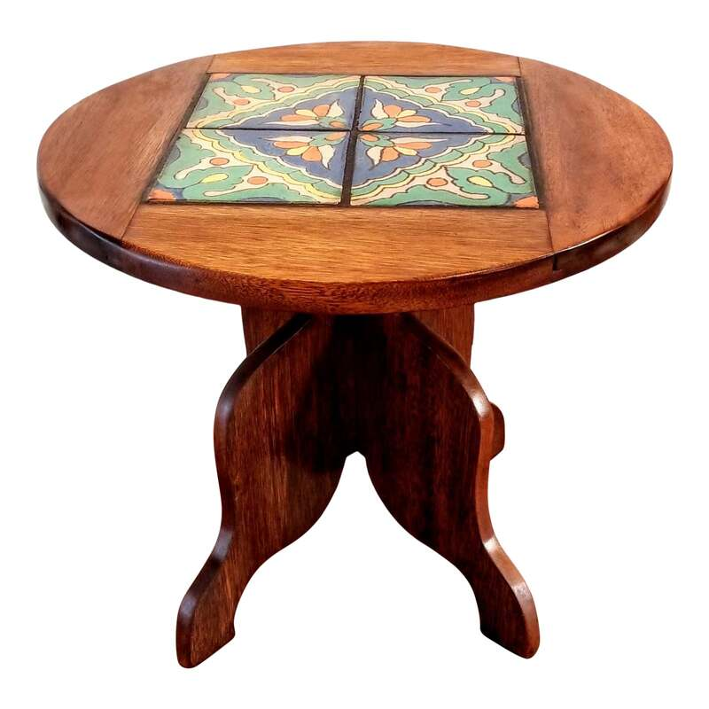 Round Spanish cedar side table in the Old California / Spanish-Colonial Revival / Mission / Monterey style. The top is inset with ceramic tiles from the Hispano-Moresque Tile Company in Los Angeles, California.  The tiles were made using the cuerda seca (dry cord) technique and are semi-gloss tin glazed. The colors are a