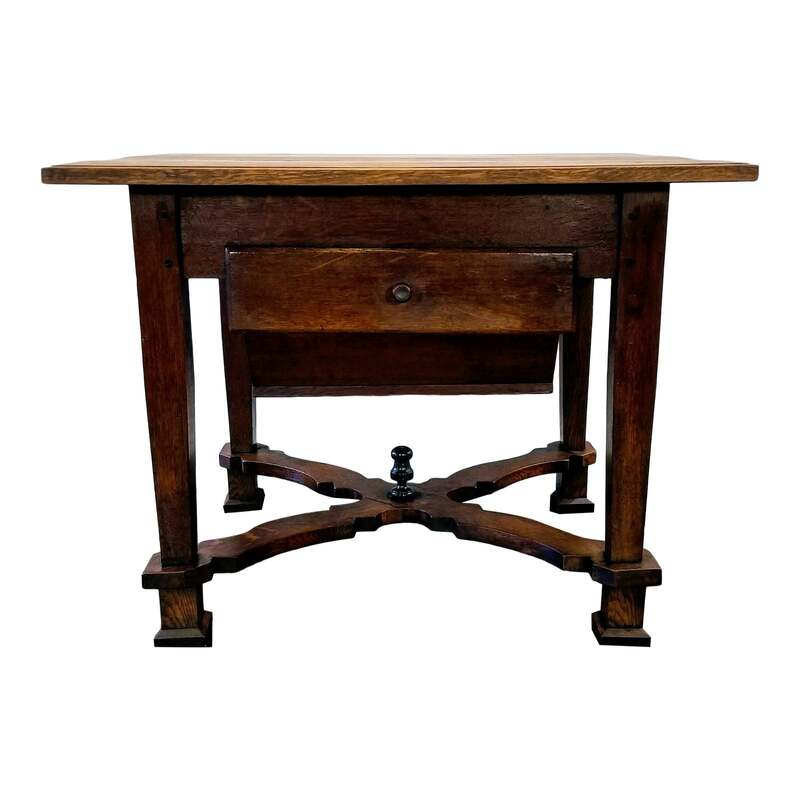 Flemish Renaissance oak kitchen work table from the area of Flanders, Northern Belgium.  This domestic table from the Low Countries was crafted between 1680 and 1749 using peg construction and features x-form shaped Flemish scroll stretchers with center finial, a Dutch-style faux bois painted ( on back and sides ) possum belly drawer ( originally to store freshly milled flour in the 17th and 18th centuries, now may store anything you please, including potatoes, onions, etc. ), and a side drawer for storage of kitchen implements.The drawers show pre-1750 construction techniques such as applied fronts, equally high sides and backs, through dovetails on backs, bottoms of front-to-back wood grain, and curved front edges. The oak finish is a natural wax.  Originally a pastry table or pantry table, this useful piece of furniture may serve as a baker's table, work table, kitchen island, and prep table.
