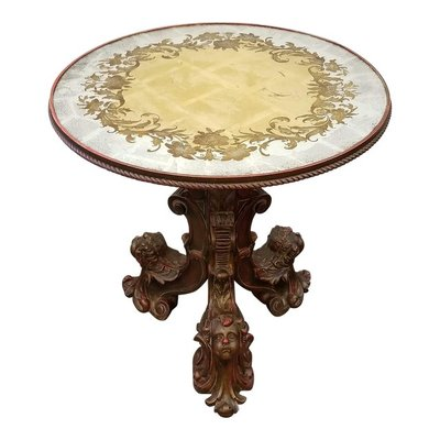 In the spirit of burgeoning neo-Maximalism, we present a gueridon harkening back to the days of original Divine Excess during the Trecento in Italy where the glass gilding technique as seen on the top of this center table was used for reliquaries. The ornate carved giltwood tripod base features putti heads and highlighting with red paint. At the top of the baluster stem sits a hand crafted verre eglomise top gilded in silver and gold with etched and painted images.