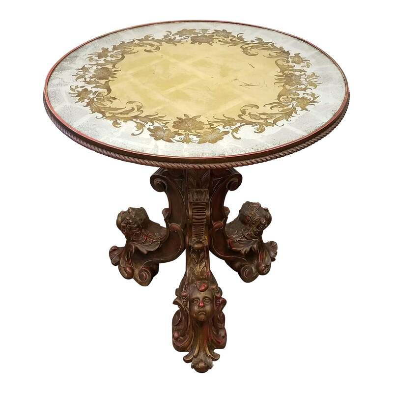 Round Italian center table with ornately carved gilt wood tripod base features putti heads and highlighting with red paint. At the top of the baluster stem sits a hand crafted verre eglomise top gilded in silver and gold with etched and painted images.
