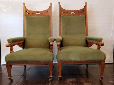 Matching pair of oversize art nouveau armchairs with deep green velvet upholstery.