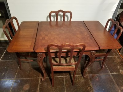 1920s French oak dining table and four chairs. Draw-leaf table has a beautiful parquetry top. Decorative scrolled apron, cabriole legs with carved knees, and soft, organic chair backs