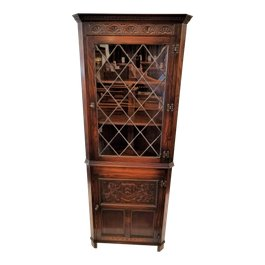 This oak corner cabinet features a glazed door on the upper cupboard. The lower cupboard door features a bas relief heraldic crest with two fishes and a lion on either side. The Jaycee owl stamp is on the back. The hinges are a classic stylized dragon motif found on English revival furniture. The original key is included.