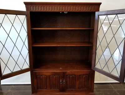 Enclosed Tudor bookcase or curiosity cabinet manufactured by Priory of Manchester. Top doors feature concave lead glass panels. Bottom cupboard doors feature the medieval linen fold motif.