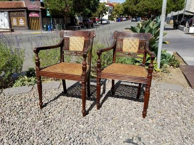 Pair carved wood Anglo-Indian caned armchairs set on gravel ground in front of street scene.